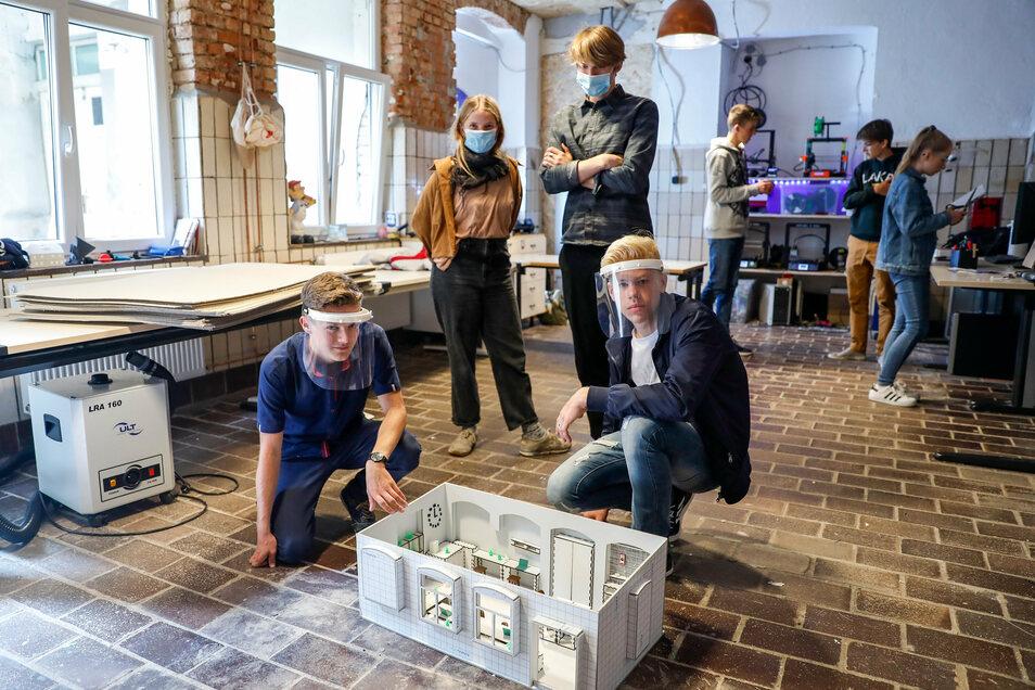 """Max Hilse, Kaya Holzmeyer, Haakon Hilse und Rubén Rejzek (von links) zeigen in der Werkstatt von """"Löbau lebt"""" ein Modell, das sie im 3-D-Drucker erstellt haben."""