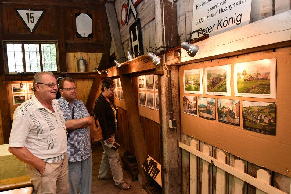 Besucher aus Liebstadt schauen sich in dem normalerweise verschlossenen ehemaligen Güterschuppen Bilder von Peter König an.