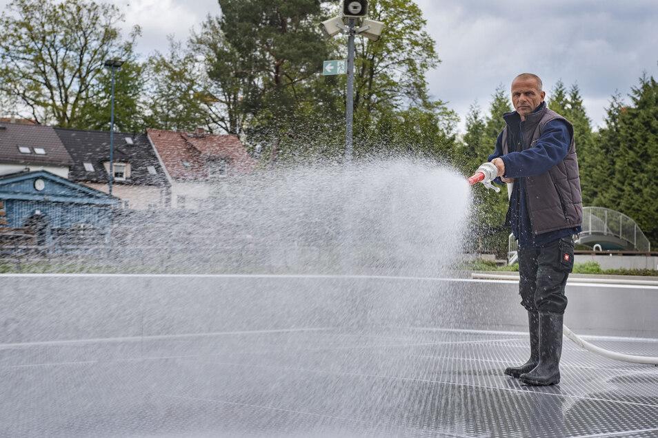 Unter Hochdruck: Schwimmmeister Gerd Lippmann vom Stadtbadverein spritzt das Planschbecken sauber. In den nächsten Tagen wird es mit Wasser gefüllt. Das Schwimmer- und das Nichtschwimmerbecken sind bereits voll. Drei Tage hat es gedauert, bis die notwendi