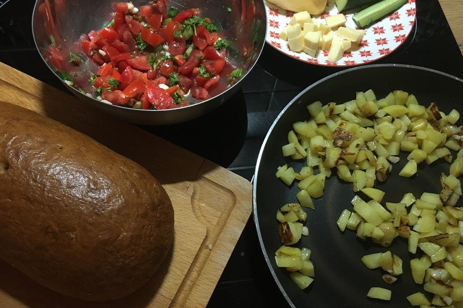 Bratkartoffeln, Käse, Brot und Rohkost ergeben ein buntes Abendessen.