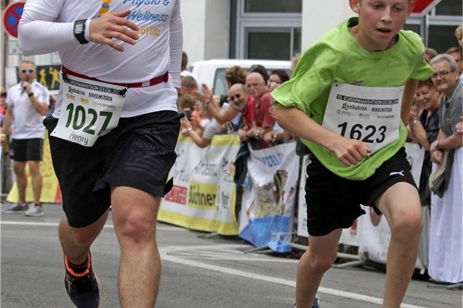 Der Olbersdorfer Henry Friede (links) feuert auf den letzten Metern des Zehn-Kilometer-Laufes Valentin Zeller an, der schließlich in 46:44 Minuten Sieger der Altersklasse U12 wurde.