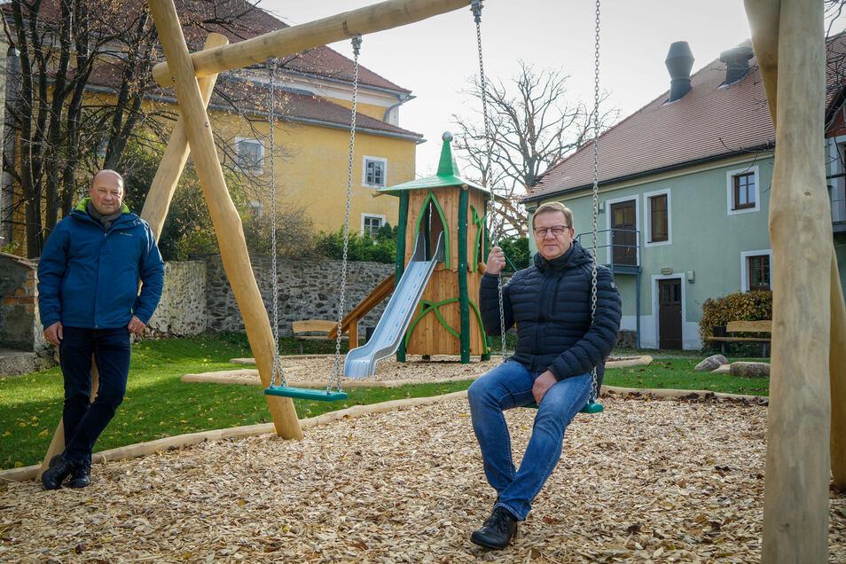 Der Neid der jungen Hochkircher ist Bürgermeister Norbert Wolf (r.) und Projektkoordinator Jens Sterzel gewiss: Der neugestaltete Platz hinterm Gemeindeamt ist noch gesperrt, aber die beiden durften schon mal schaukeln.