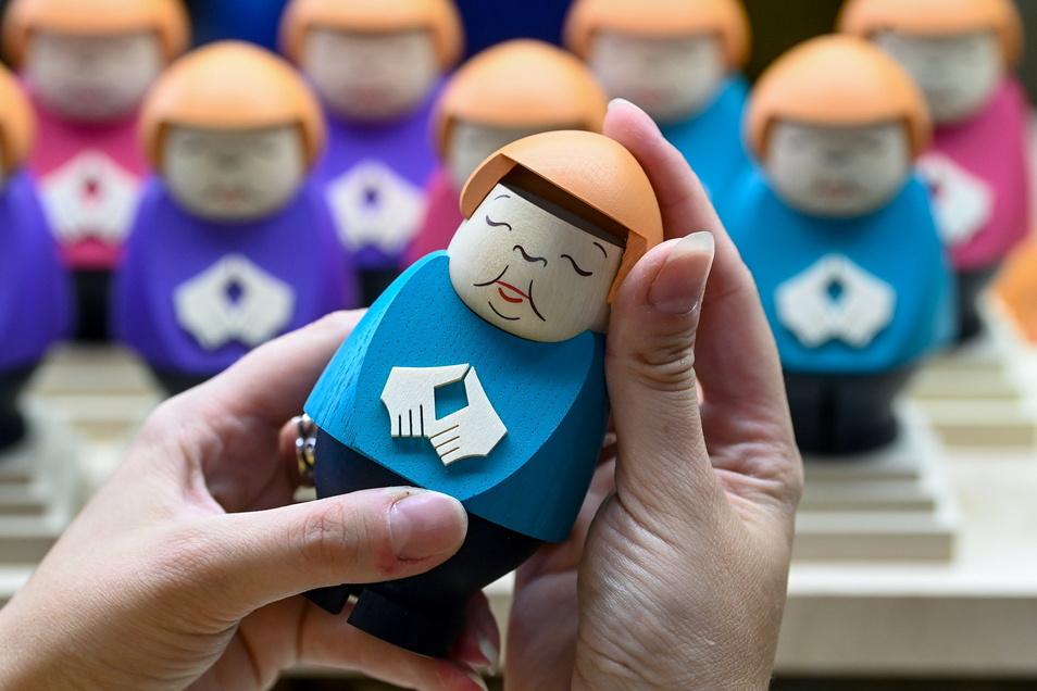 Sina Klement komplettiert in der Schauwerkstatt der Seiffener Volkskunst eine Angela-Merkel-Räucherfigur.