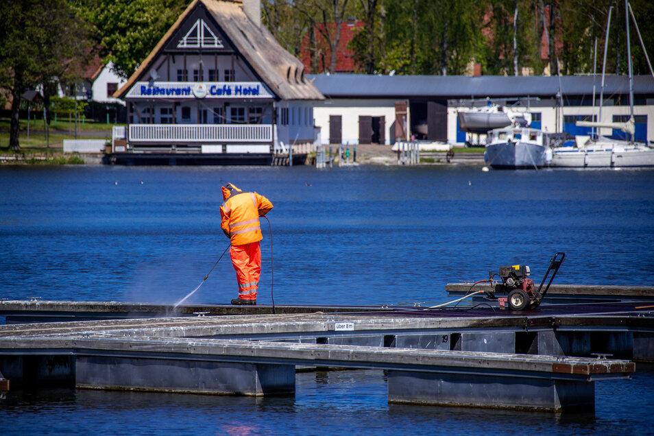 Mit einem Hochdruckreiniger putzt ein Mann einen leeren Bootssteg im Stadthafen an der Müritz. Die Tourismusbetriebe an der Mecklenburgischen Seenplatte bereiteten sich auf Corona-Lockerungen vor.