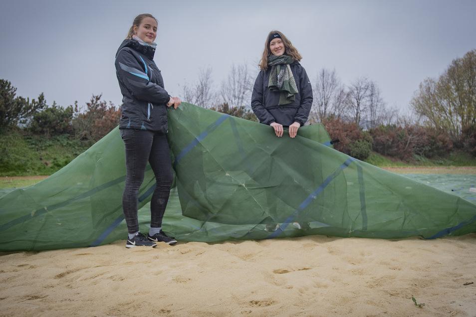 Die Gymnasiastinnen Katharina Ullrich (l.) und Anne Kurzetz haben den neuen Beachvolleyballplatz in den Winterschlaf geschickt und den Spezialsand mit einer Plane abgedeckt, um ihn zu schützen.