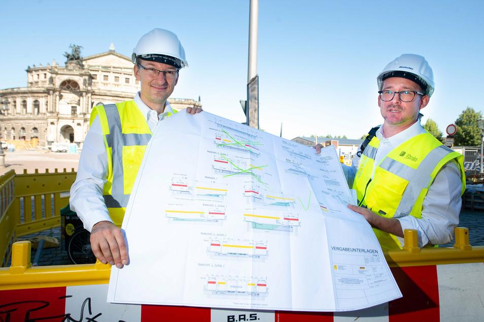 Straßenbauamtschef Robert Franke (l.) und Baubürgermeister Raoul Schmidt-Lamontain zeigen einen Bauplan mit den Etappen auf der Augustusbrücke. Die Arbeiten dauern länger und sind teurer geworden.