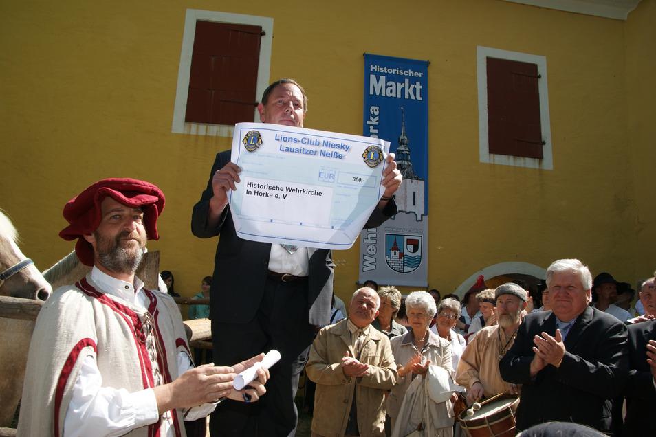 Harald Schwarz überreicht 2011 bei der Eröffnung des historischen Markts an der Wehrkirche in Horka einen Scheck des Lions-Club Niesky. Archivfoto:: Arkadius Guzy