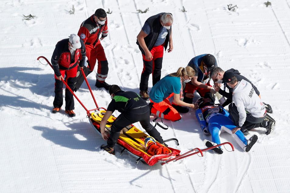 Sanitäter kümmern sich um Daniel Andre Tande aus Norwegen, nachdem er gestürzt ist. Der Skiflug-Weltmeister ist im slowenischen Planica schwer gestürzt und musste ins Krankenhaus gebracht werden.