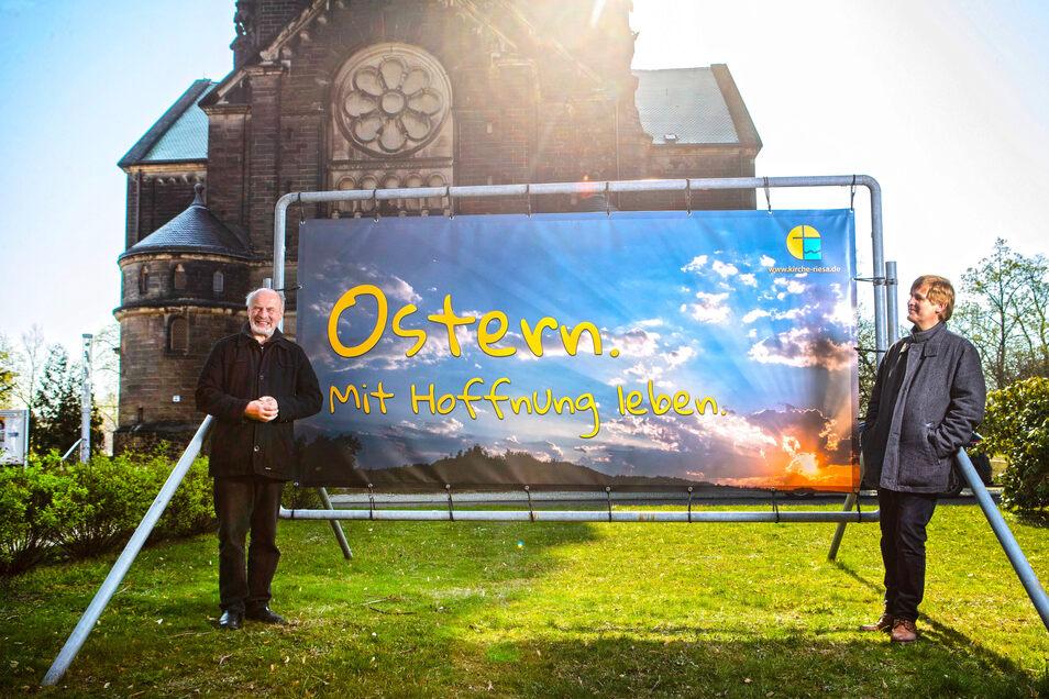 Osterfreude trotz Corona-Furcht: Pfarrer Gunter Odrich (l.) und Kantor Sebastian Schwarze-Wunderlich haben am Dienstag vor der Riesaer Trinitatiskirche dieses Plakat angebracht.