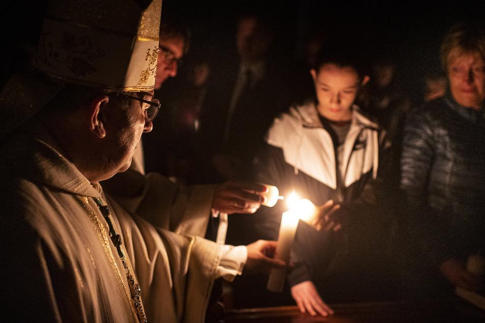 Osterfeuer in der St. Jakobus Kathedrale. Bischof Wolfgang Ipolt spendet Feuer zum Anzünden der Kerzen bei einer Messe in Görlitz