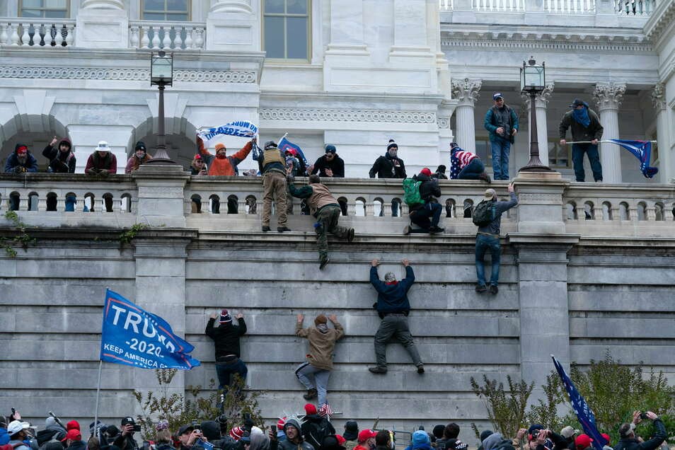 Anhänger von Präsident Donald Trump klettern in Washington auf die Westwand des US-Kapitols.