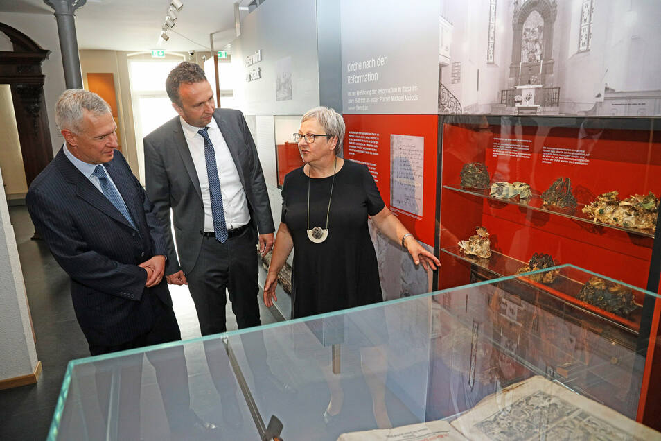 Museums-Chefin Maritta Prätzel erklärt Riesas Oberbürgermeister Marco Müller (CDU, M.) und Sparkassenvorstand Rainer Schikatzki die Objekte aus der Klostergruft, die in der Dauerausstellung zu besichtigen sind.