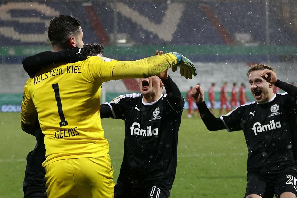 Kiels Torwart Ioannis Gelios, Fabian Reese und Jannik Dehm (l-r) feiern ihren Sieg nach Elfmeterschießen.