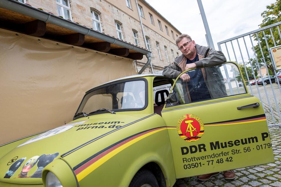 Conny Kaden, Inhaber des DDR-Museums in Pirna, steht an einem Trabi mit Werbung des Museums. Er sucht für die nächste Saison neue Mitarbeiter.