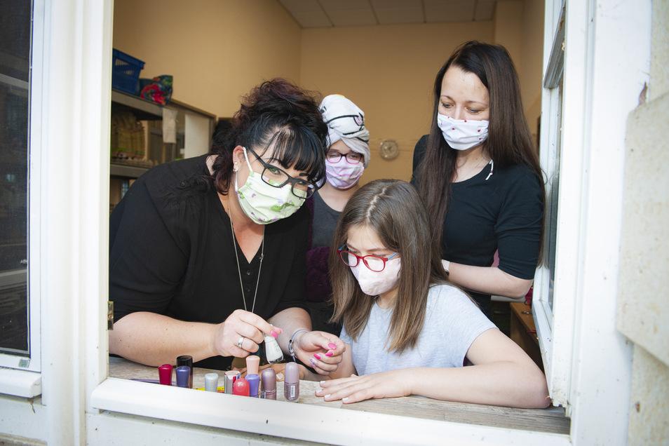 Marie (13) bekommt die Fingernägel von Janette Held lackiert, Janine Schlegel (r.) schaut zu.