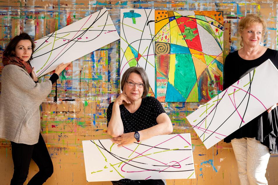 Franziska Woyke, Leiterin der FBS, Eva-Maria Grohmann und Patricia Hartmann (von links) zeigen die Segmente für das große Mosaikbild, das in der laufenden Jubiläumswoche gestaltet wird. Die Besucher sind eingeladen, zu Farbe und Pinsel zu greifen und die