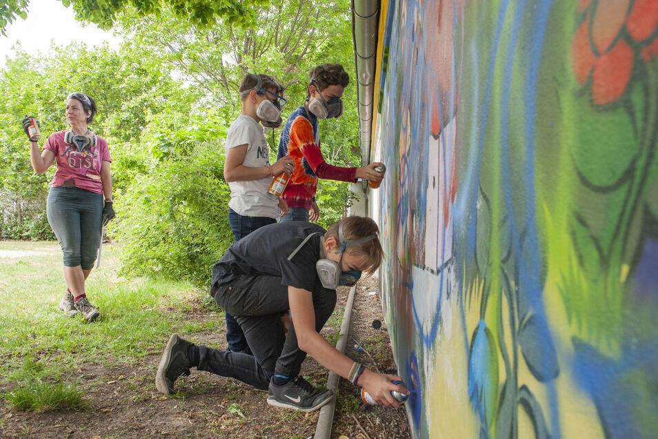Die Graffiti-Sprayer gestalten eine Wand am Spielplatz im Preuskerviertel: hier Andrea Kotztin und Jarin, Halgrim und Julian aus Meißen.