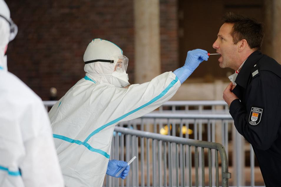 Einem Mitarbeiter der Berufsfeuerwehr Köln wird im dritten Infektionsschutzzentrum der Stadt Köln mit einem Stäbchen ein Abstrich für einen Test auf den Coronavirus entnommen.