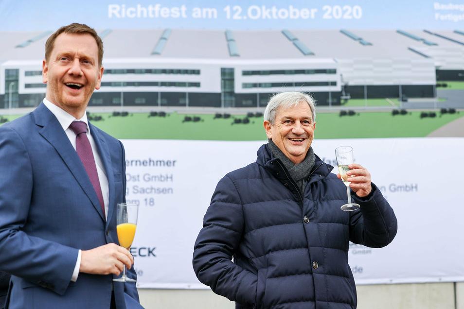 Michael Kretschmer (l, CDU), Ministerpräsident von Sachsen, und Fritz Dräxlmaier, Inhaber des Familienunternehmens, heben ihre Gläser zum Richtfest des im Bau befindlichen Produktionswerks für Hochvolt-Batteriesysteme des Automobil-Zulieferers Dräxlmaier.