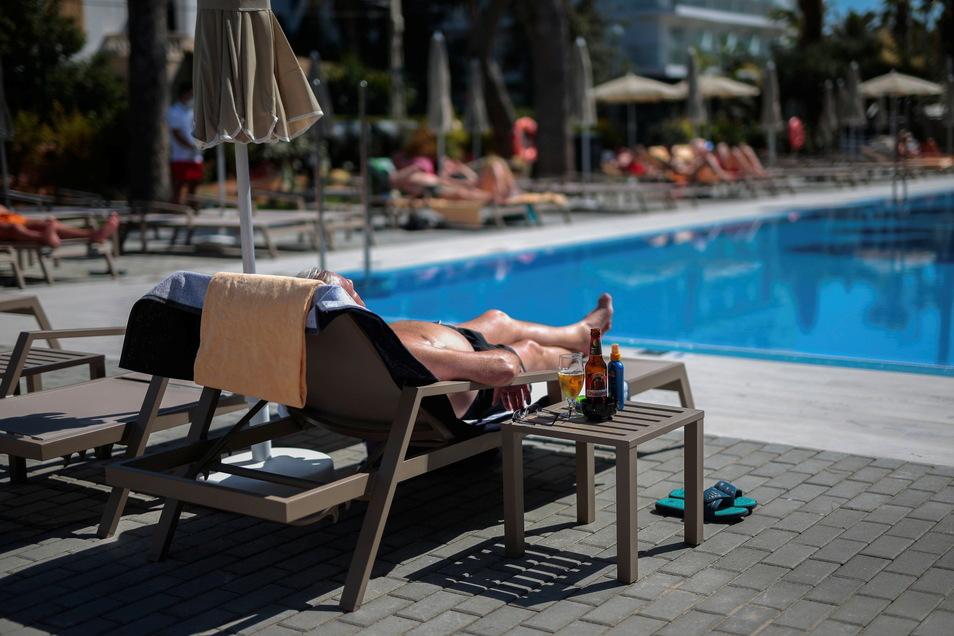 Ein deutscher Tourist sonnt sich am Schwimmbad seines Hotels in Palma de Mallorca.
