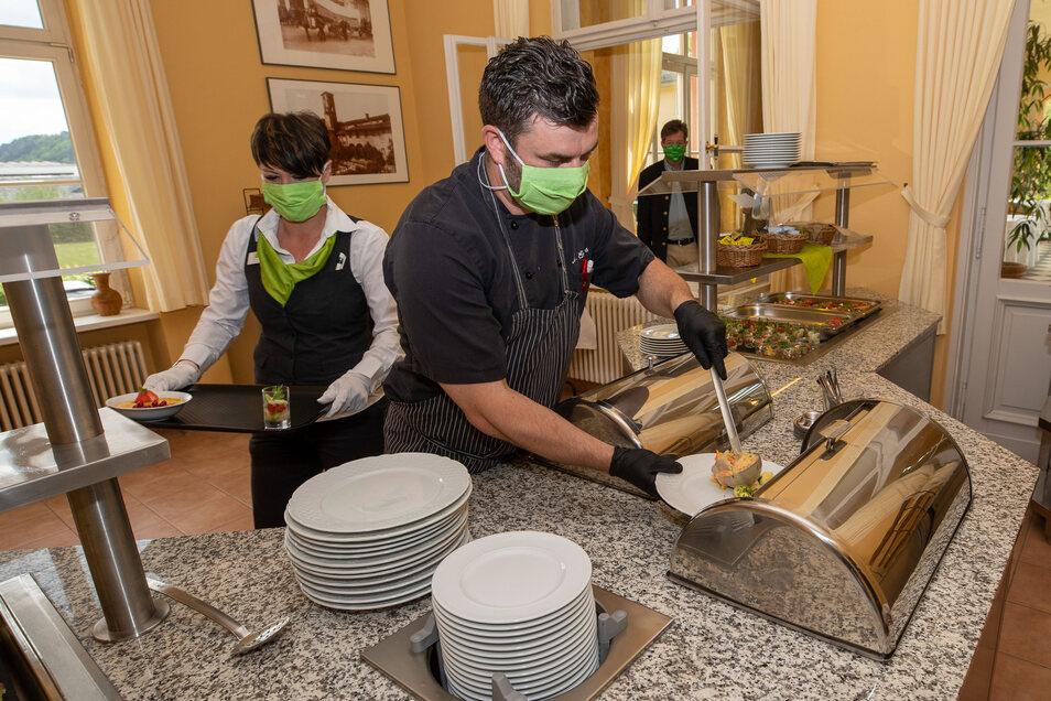 Manuel Enders gibt das Essen auf den Teller, während Mareen Funke das Tablett befüllt, das den Gästen zum Frühstück an den Tisch gebracht wird.