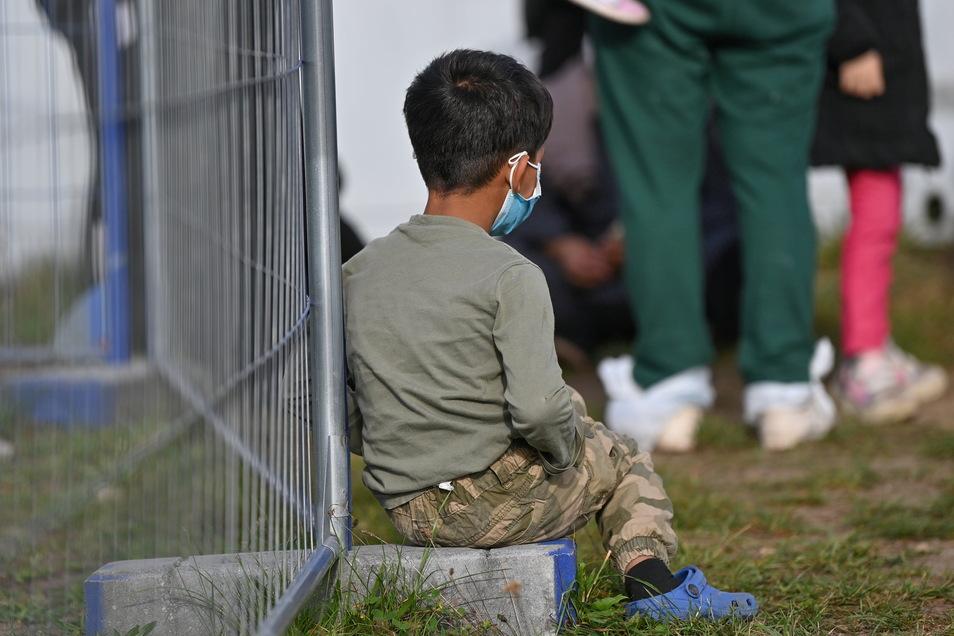 Ein Junge sitzt an einem Zaun in der Zentralen Erstaufnahmeeinrichtung für Asylbewerber in Eisenhüttenstadt.
