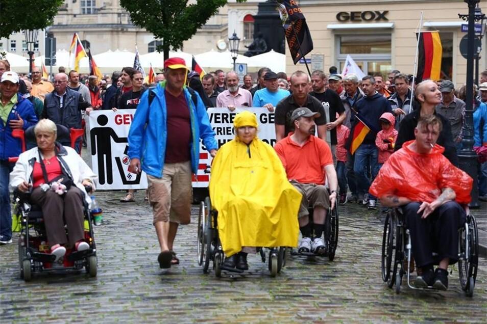 Vor den Montagsspaziergängern von Pegida fahren Rollstühle her.