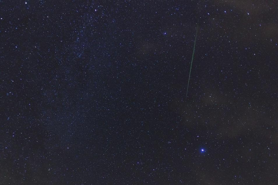 Ein heller Perseidenmeteor am 6. August 2019 in der Nähe des Sternbildes Leier. Der helle Stern unterhalb ist die Wega, der Hauptstern des Sternbildes. Typisch für die Perseiden ist das grüne Leuchten der Bahn.