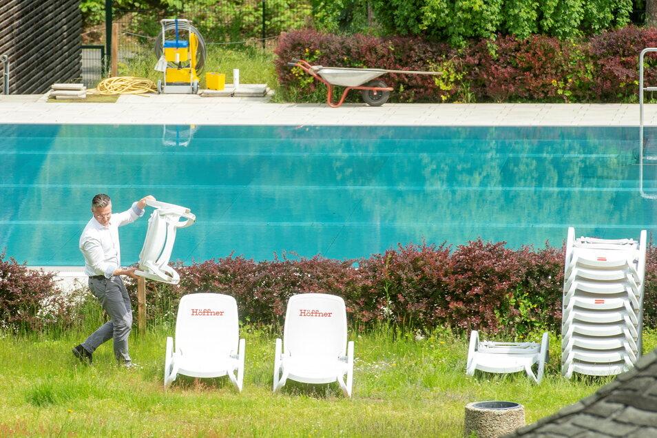 Das Bilzbad in Radebeul ist für die neue Freibadsaison vorbereitet und sbf-Geschäftsführer Titus Reime stellt Liegestühle neben dem Inselbecken für die ersten Badegäste auf.