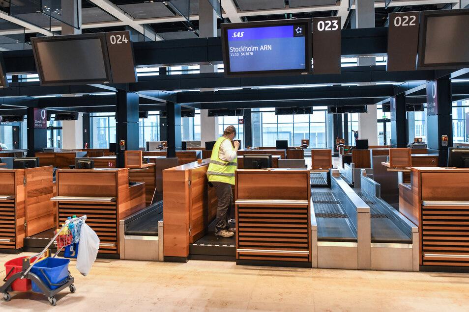 Eine Angestellte einer Reinigungsfirma säubert einen Check-in-Schalter im Terminalgebäude des Hauptstadflughafens Berlin Brandenburg Willy Brandt (BER).