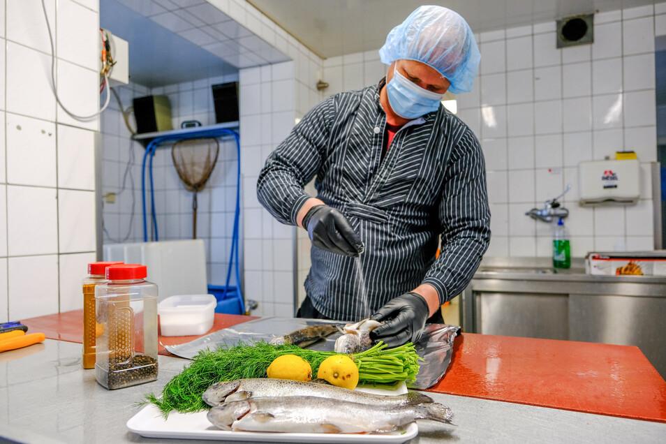 Henry Lindner, Chef der Teichwirtschaft, würzt Forellen für den Verkauf im Hofladen Bärnsdorf.