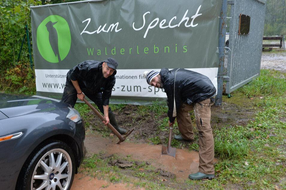 Carlo Schwarze (rechts) und Thomas Liebschner legen mit Spaten und Spitzhacke die Drainage frei.