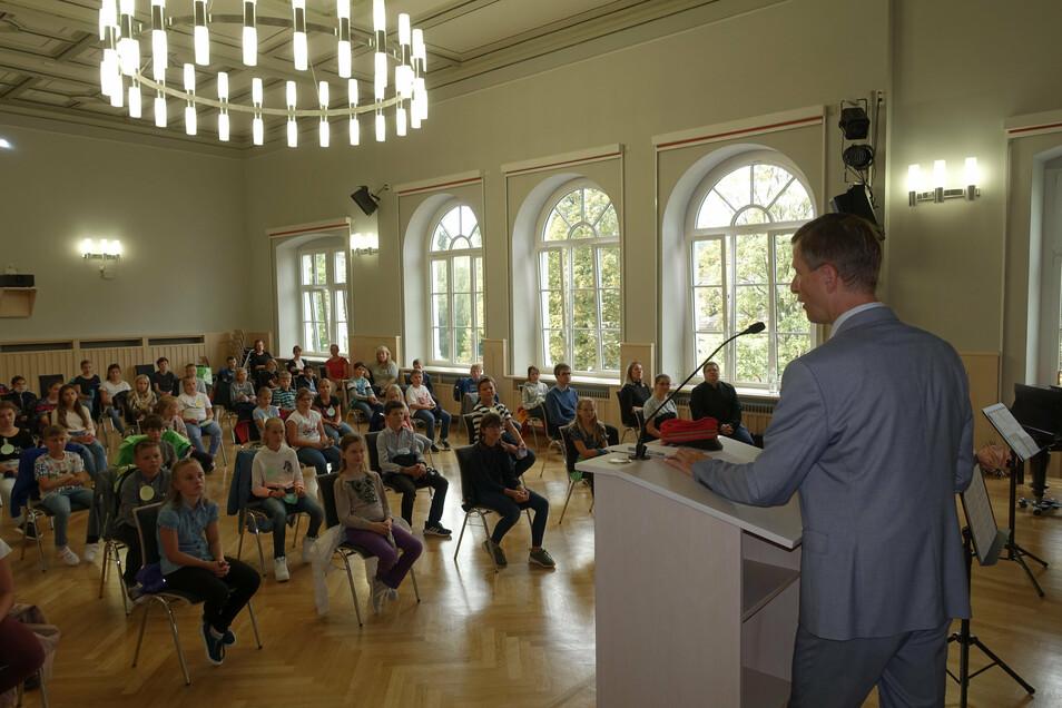 Jeweils zwei der vier neuen fünften Klassen habe bei der Aufnahmefeier in der Aula Platz genommen.