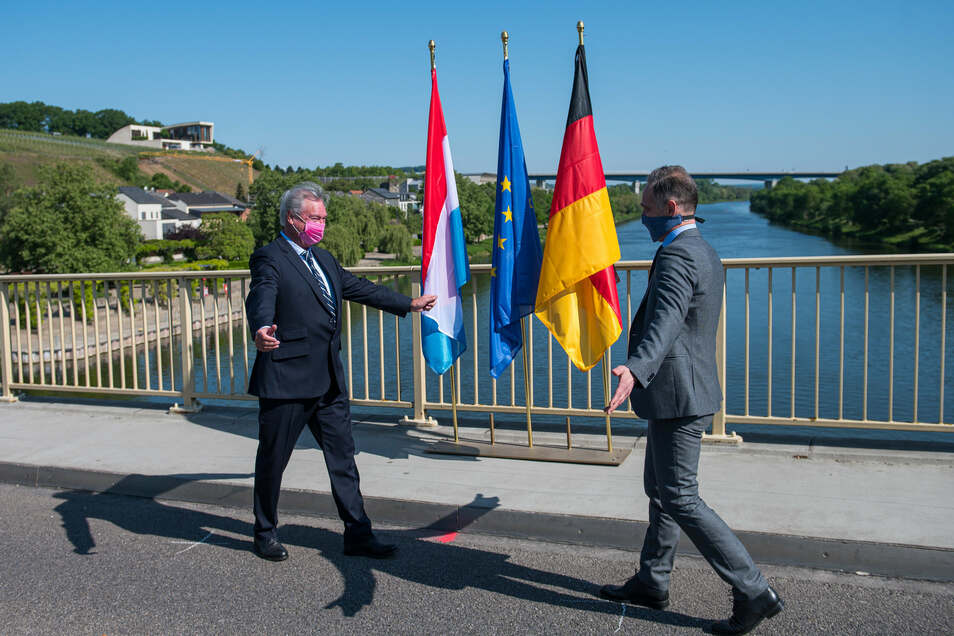 Jean Asselborn (l) und Heiko Maas (SPD) trafen sich auf der Brücke über die Mosel, die das saarländische Perl und das Luxemburger Schengen verbindet. In der Nacht wurden die Grenzen zwischen Deutschland und Luxemburg wieder geöffnet.