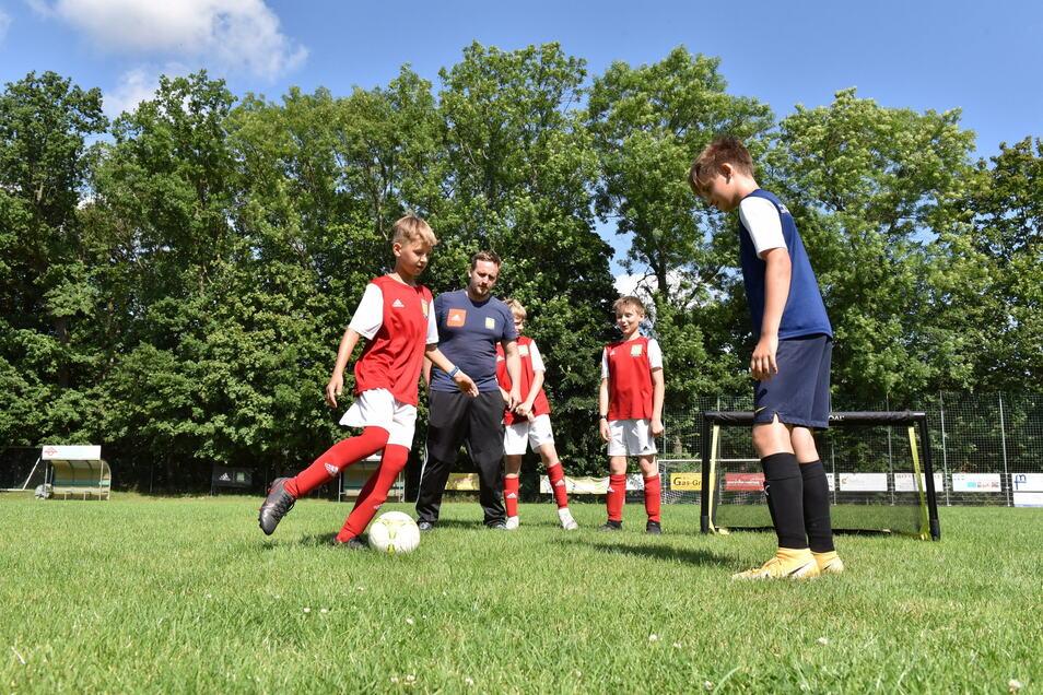 26 Kinder nehmen diese Woche am Fußball-Nachwuchscamp auf dem Sportplatz in Reinhardtsgrimma teil unter Anleitung von Nico Sacher (2. v.l.)