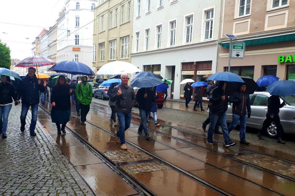 Bei strömendem Regen fand am Montag der Protest-Spaziergang in Görlitz statt, der unter anderem über die Berliner Straße führte. Mittig im Bild ist AfD-Stadtrat Jens Jäschke zu sehen.