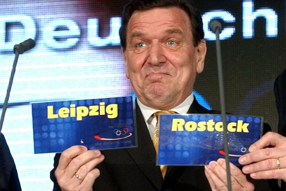 Bundeskanzler Gerhard Schröder präsentiert die Siegerstädte – und schaut dabei überrascht. In Rostock sollten die Segelwettbewerbe ausgetragen werden.