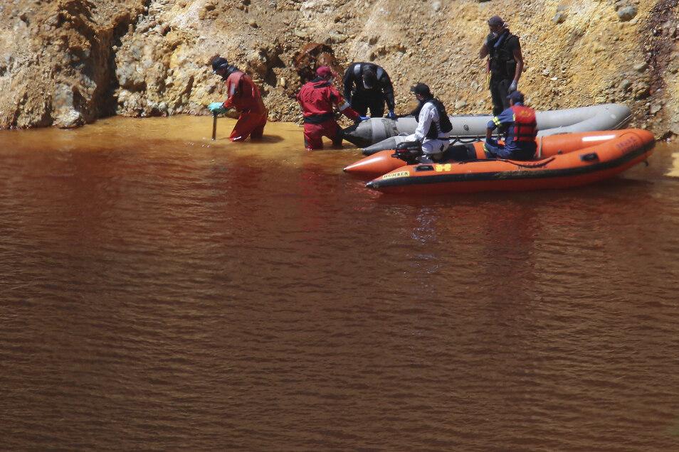 Taucher und Polizisten durchsuchen einen Baggersee, nach weiteren Koffern, in denen Leichenteile vermutet werden.