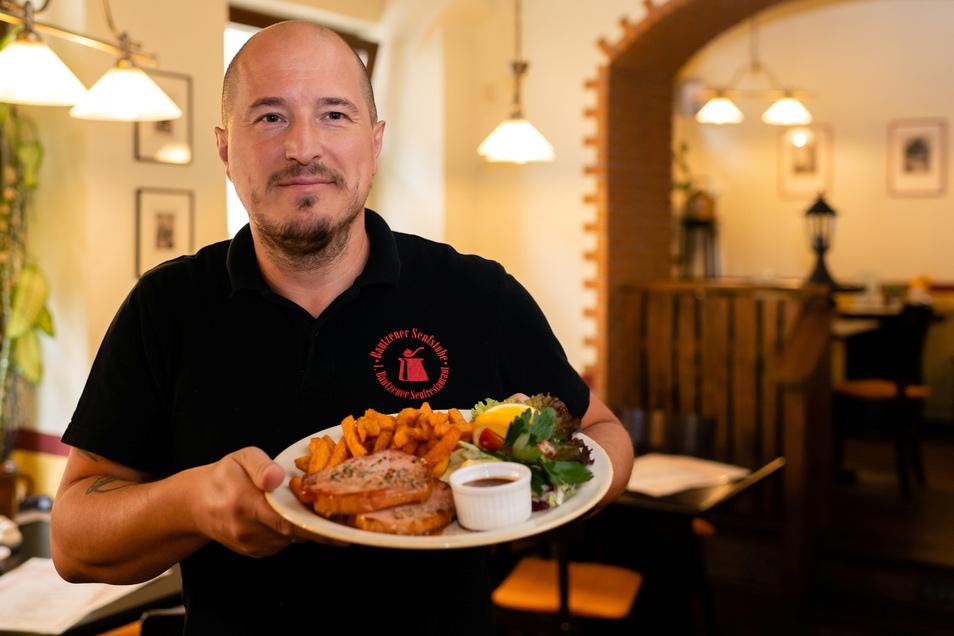 Küchenchef Sten Lindgrön von der Bautzener Senfstube präsentiert Kasslersteak mit Orangen-Senf-Soße und Süßkartoffel-Pommes.