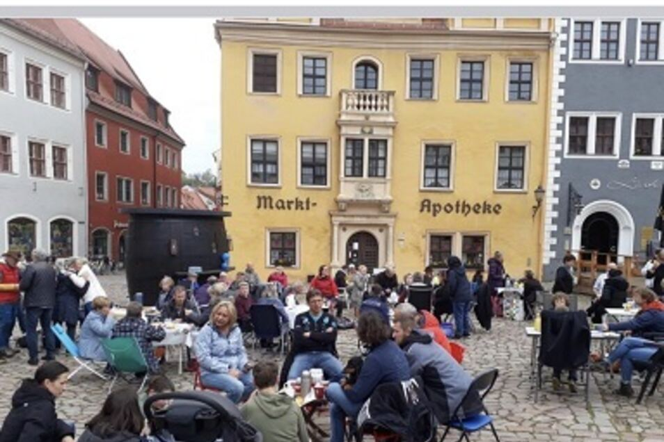 Dicht gedrängt sitzen Menschen auf dem Meißner Markt.