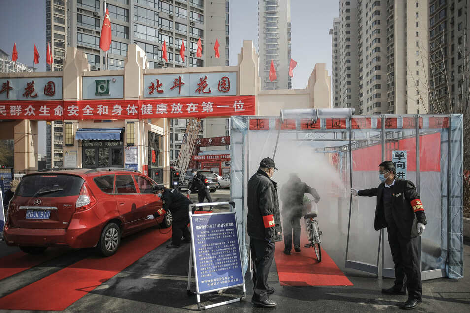 Sicherheitskräfte öffnen einem Radfahrer den Zugang zu einer temporär eingerichteten Desinfektionsstation in der Stadt Tianjin.