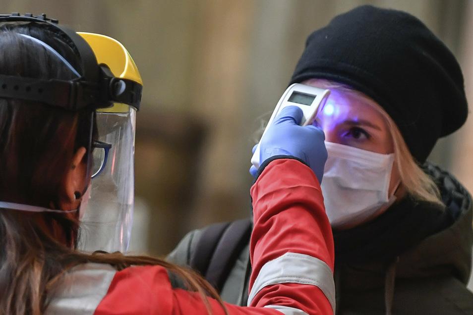 Eine Mitarbeiterin des Roten Kreuzes überprüft auf dem Mailänder Hauptbahnhof am Zugangsbereich für Zugabfahrten die Temperatur einer Frau.