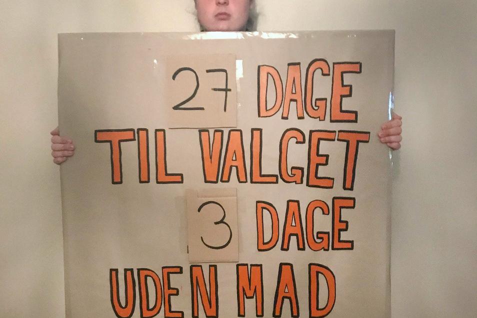 """Mikkel Brix hält ein Schild mit der Aufschrift """"27 Tage bis zur Wahl, drei Tage ohne Essen"""". Im Kampf gegen die Klimakrise ist der Däne in den Hungerstreik getreten."""