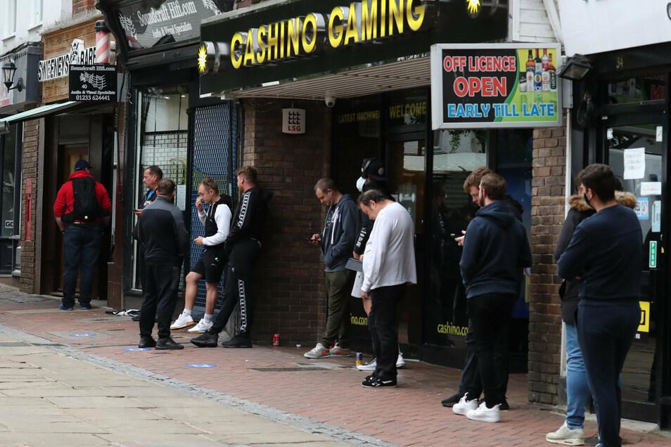 Menschen warten in Ashford auf die Wiedereröffnung eines Barbiers.