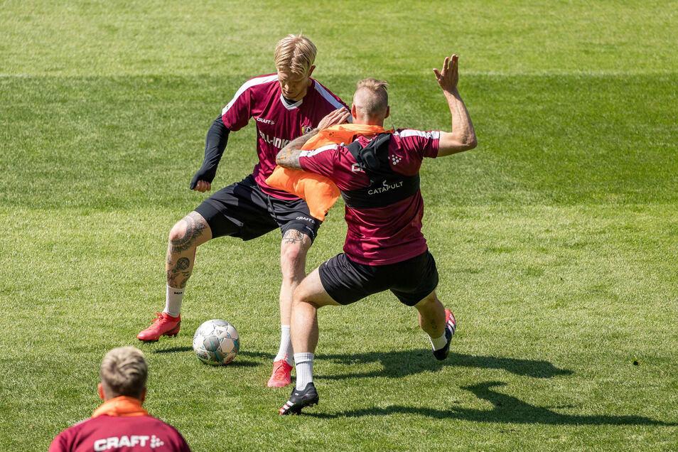 Schluss mit Abstand: Im ersten Mannschaftstraining nach der Corona-Zwangspause kommen sich Dynamos Simon Makienok (l.) und Brian Hamalainen im Zweikampf nahe.