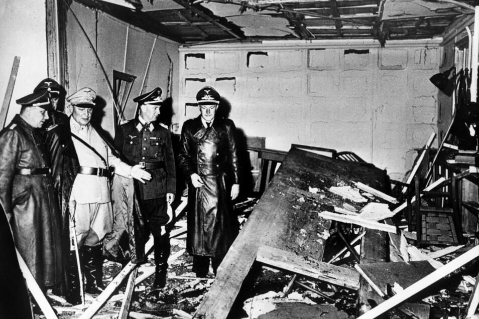 """Reichsmarschall Hermann Göring (helle Uniform) und der Chef der """"Kanzlei des Führers"""", Martin Bormann (li.), begutachten die Zerstörung der Karten-Baracke im Führerhauptquartier nach dem Sprengstoff-Attentat auf Hitler."""