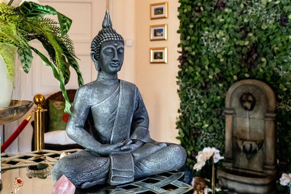 Ein Buddha auf einer Lotusblüte begrüßt Besucher im mondänen Empfangsbereich.