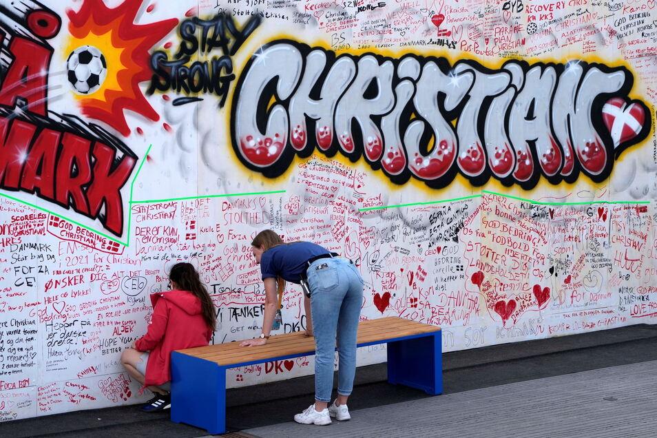 Menschen schreiben an eine Wand in der Fanzone in Kopenhagen gute Wünsche für den dänischen Spieler Christian Eriksen.