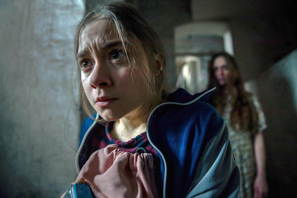 Talia (Hannah Schiller) angsterfüllt im Schulkeller, hinter ihr der Geist von Marie Kunz (Franziska Junge).