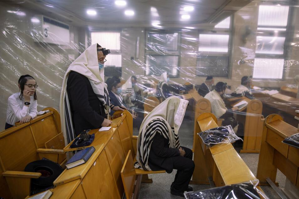 Ultra-orthodoxe Juden sitzen während eines Morgengebets in einer Synagoge, die aufgrund von Corona-Maßnahmen auf zwanzig Personen beschränkt wurde.